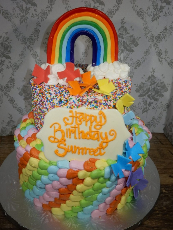 Colorful Rainbow Cake by Goodies Bakeshop decorated with buttercream, sprinkles and hand made fondant decorations